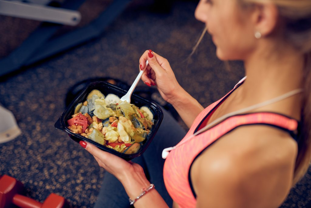 woman in fitness clothes eating healthy food