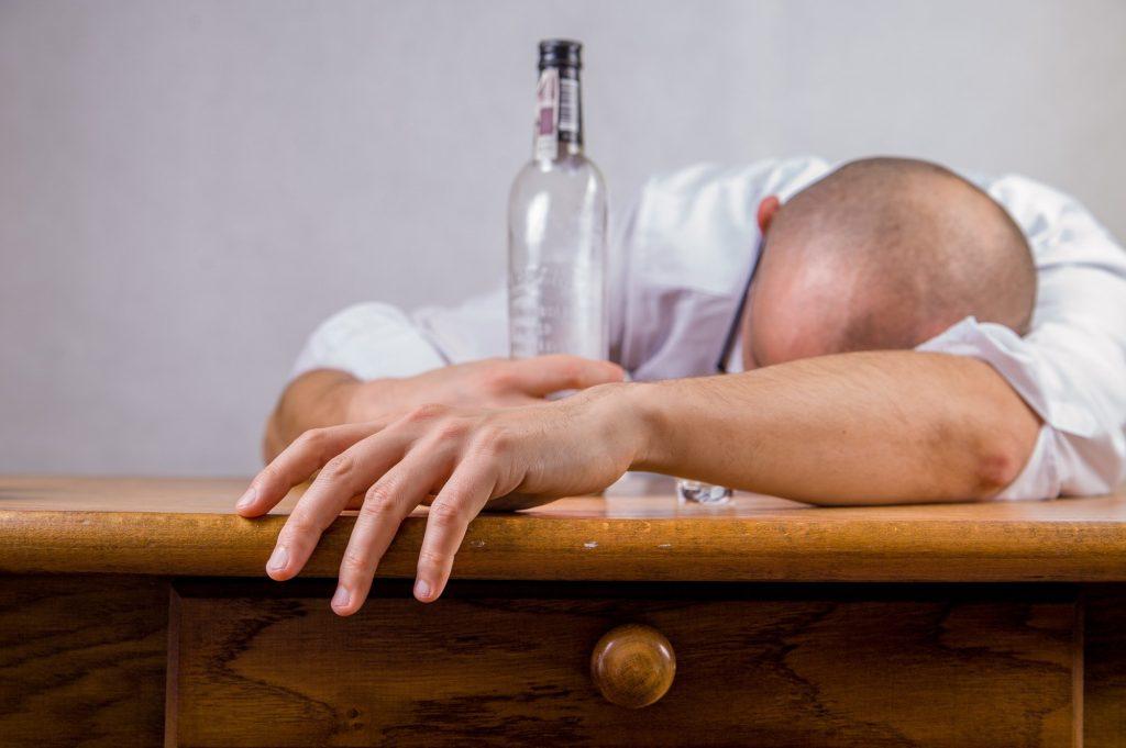 man with drug addiction slumped on table