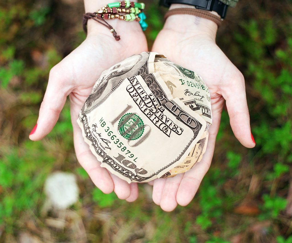 person holding ball of money