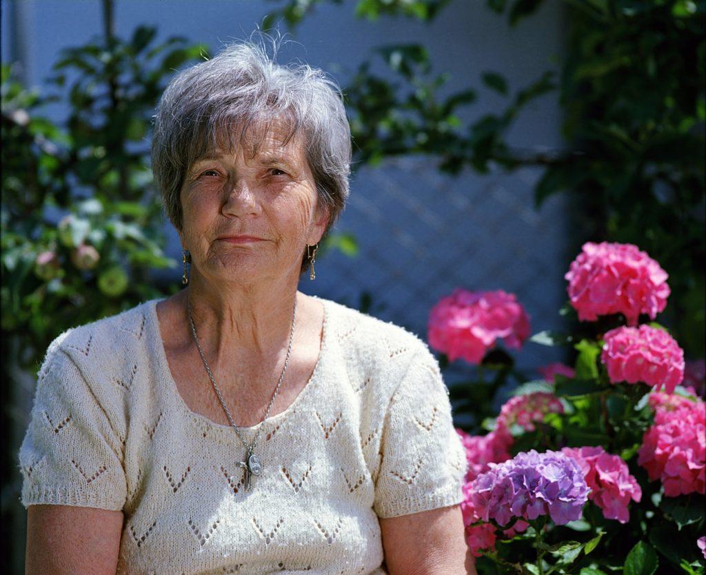 elderly woman sitting near flowers